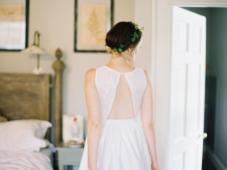 Bride looking in mirror with split back dress