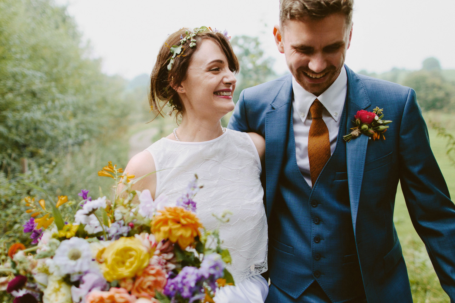bride and groom walking arm in arm with colourful bouquet