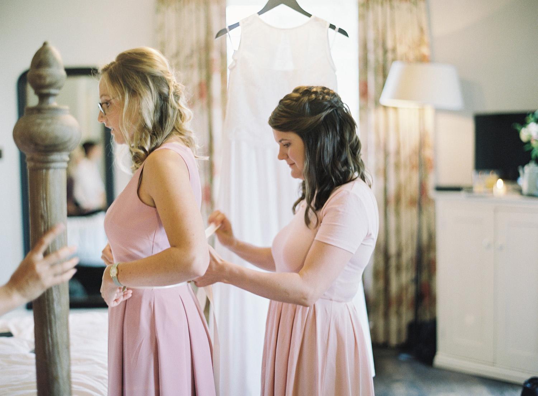 bridesmaids tying up dresses