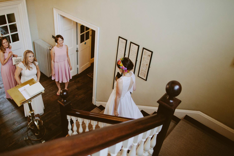 bridesmaids watching bride walk down steps of hotel