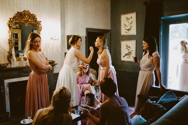 bride putting make up on bridesmaid