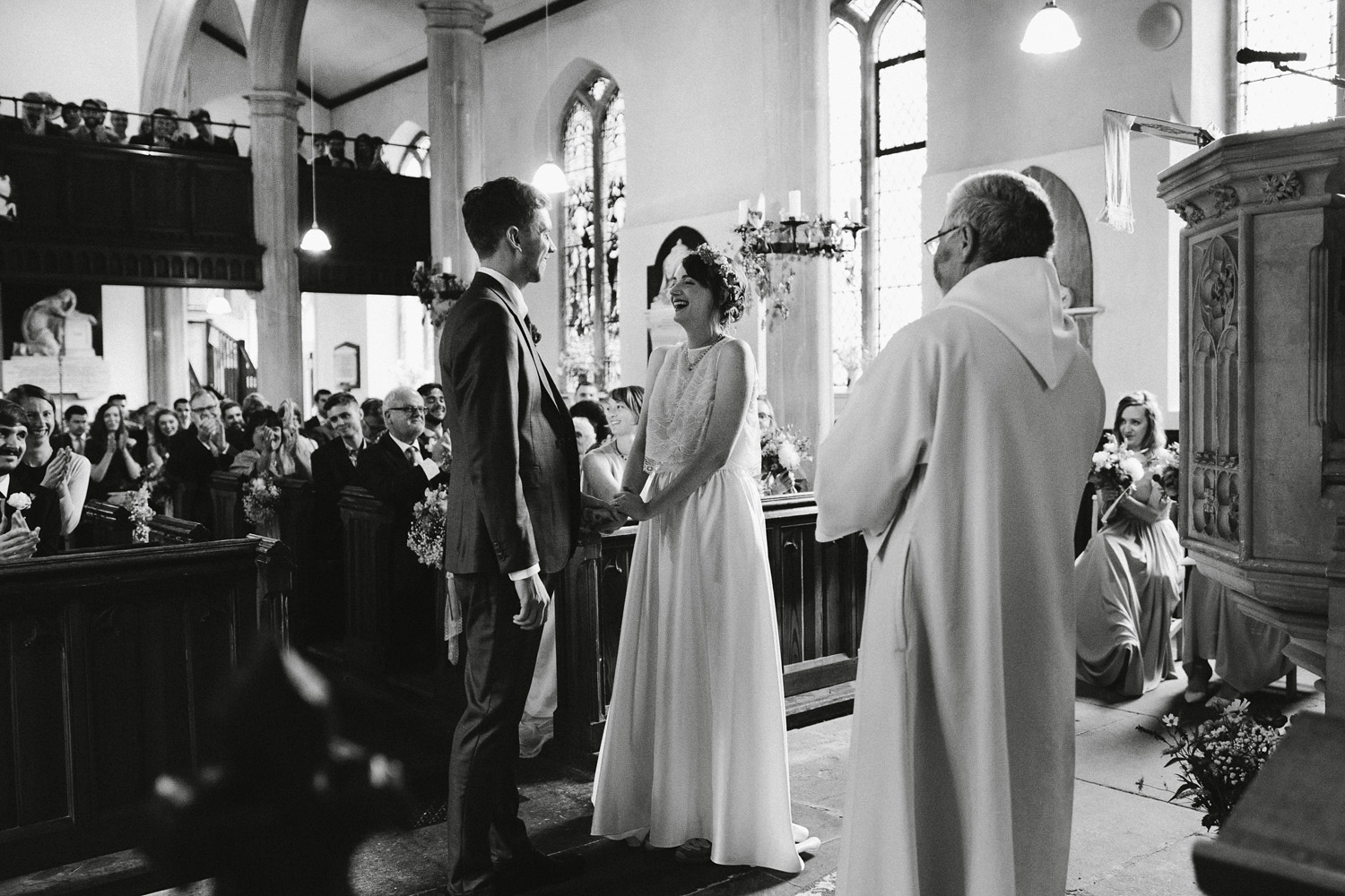 bride and groom laughing at front of church