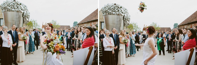 bride throwing her bouquet to wedding guests at Hauser & Wirth Somerset wedding