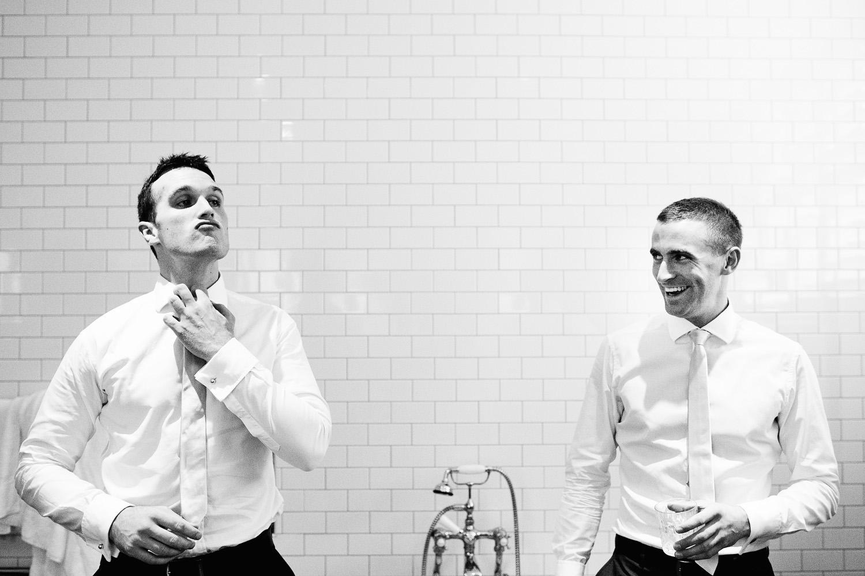 groom laughing at best man in bathroom