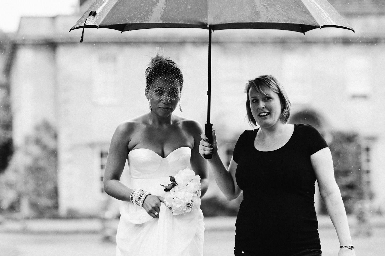 bride walking to church under umbrella at Somerset wedding
