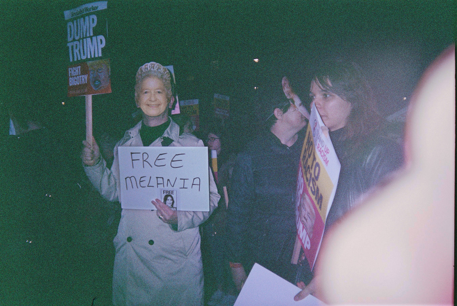 """person with Queens face mask holding sign that reads """"free Melania"""""""