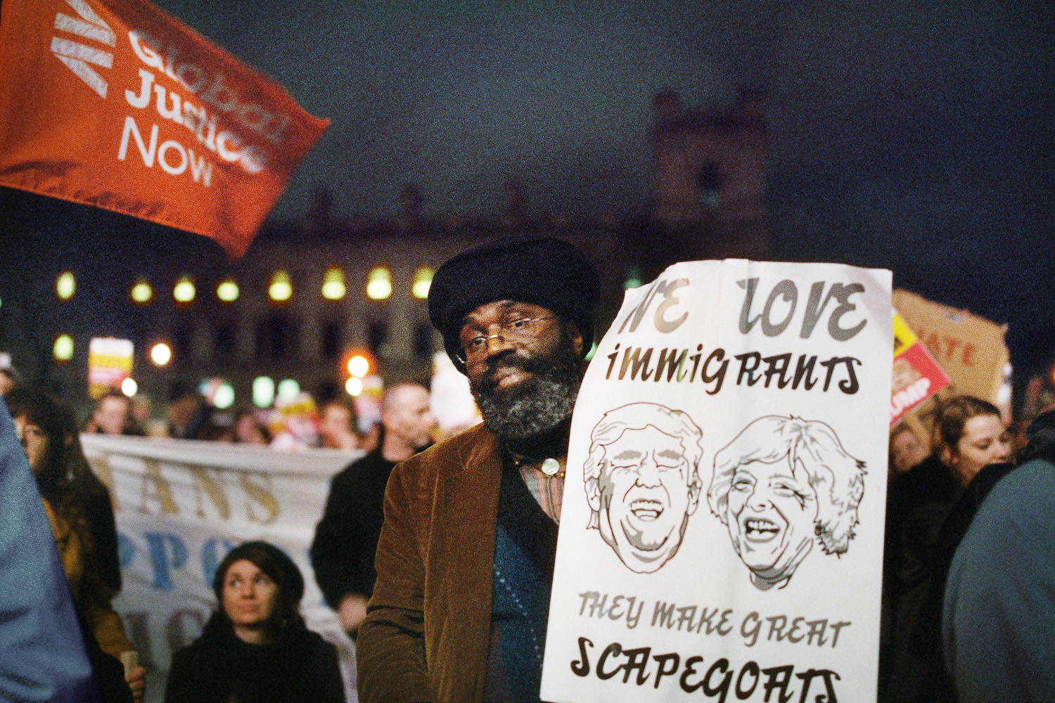 Black man holding placard with the faces of Trump and Theresa May
