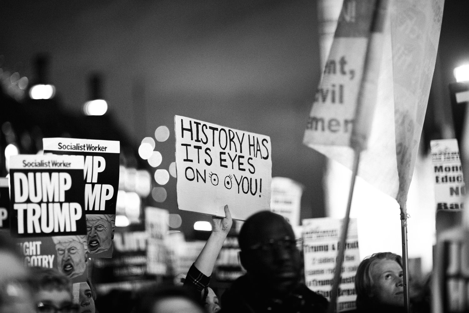 lots of placards held up at London march against Donald Trump