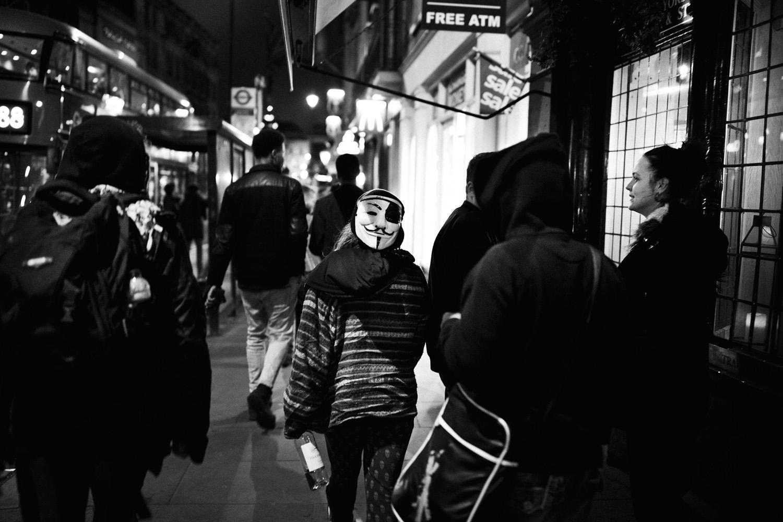 teenager wearing Guy Fawkes mask on London street