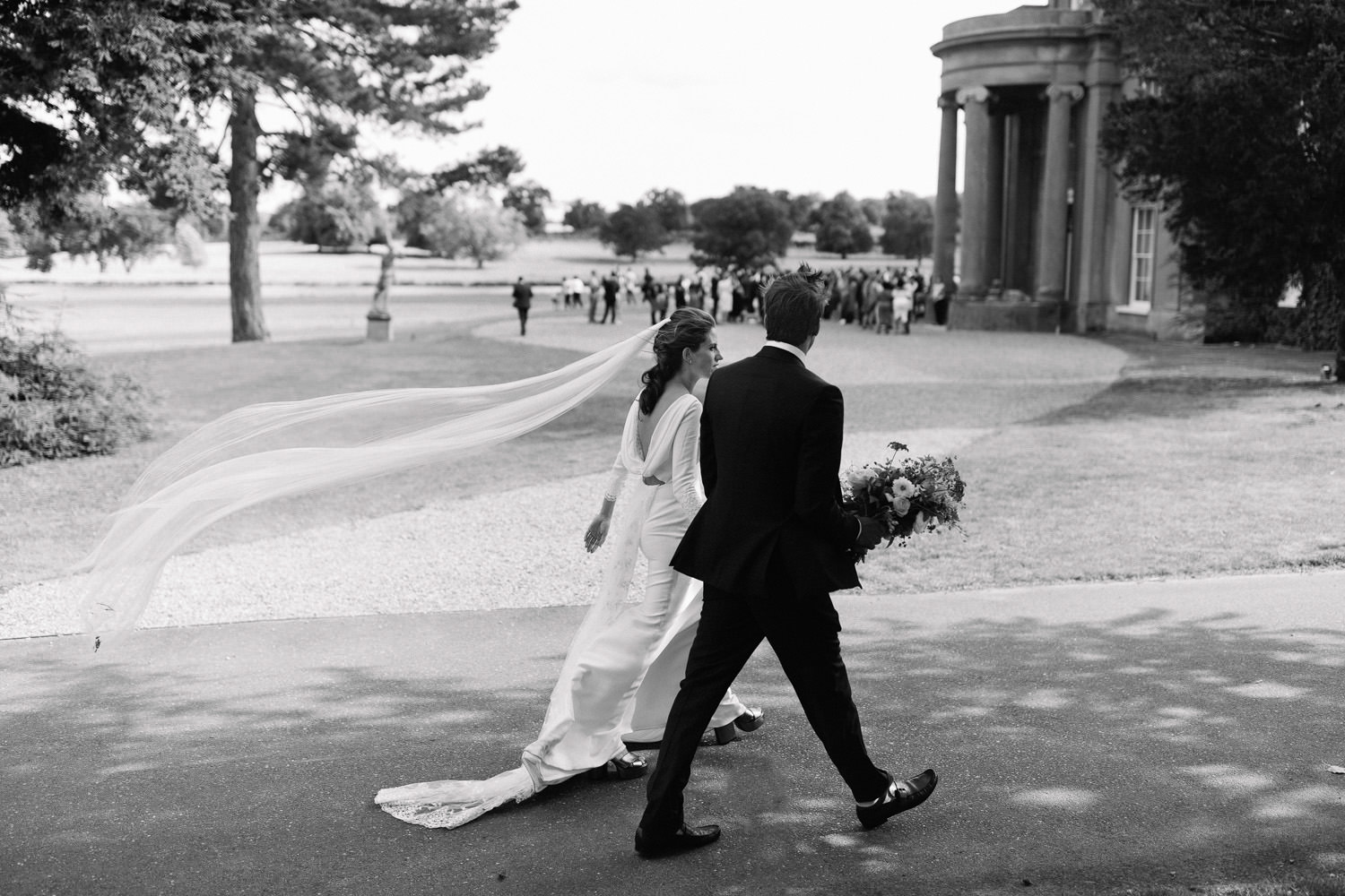 Bride and groom walk to wedding venue with veil blowing in the wind