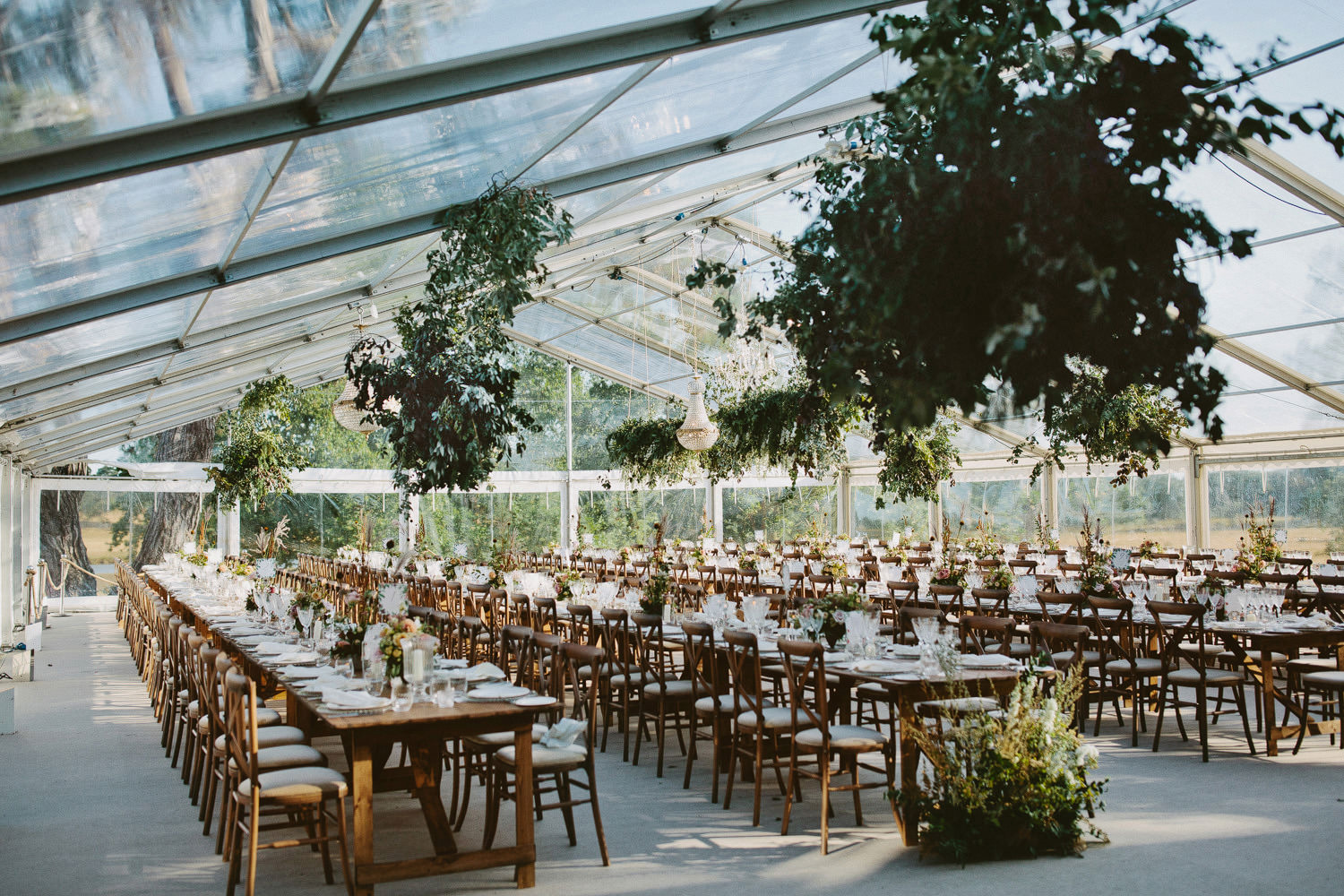 Reception dining room with hanging greens in clear marquee at Wilderness Reserve