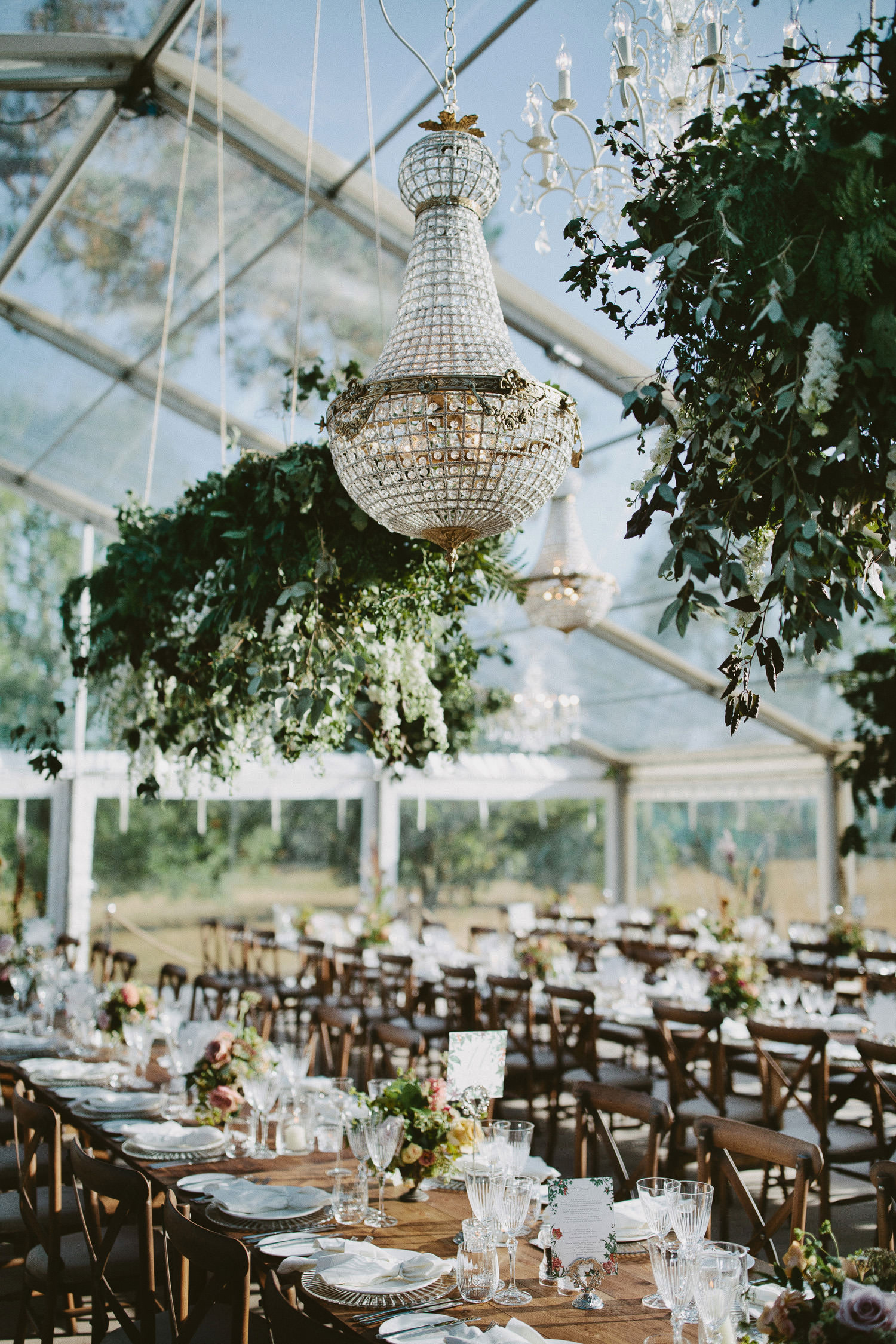 Chandeliers hanging in clear marquee with natural florals over wedding tables