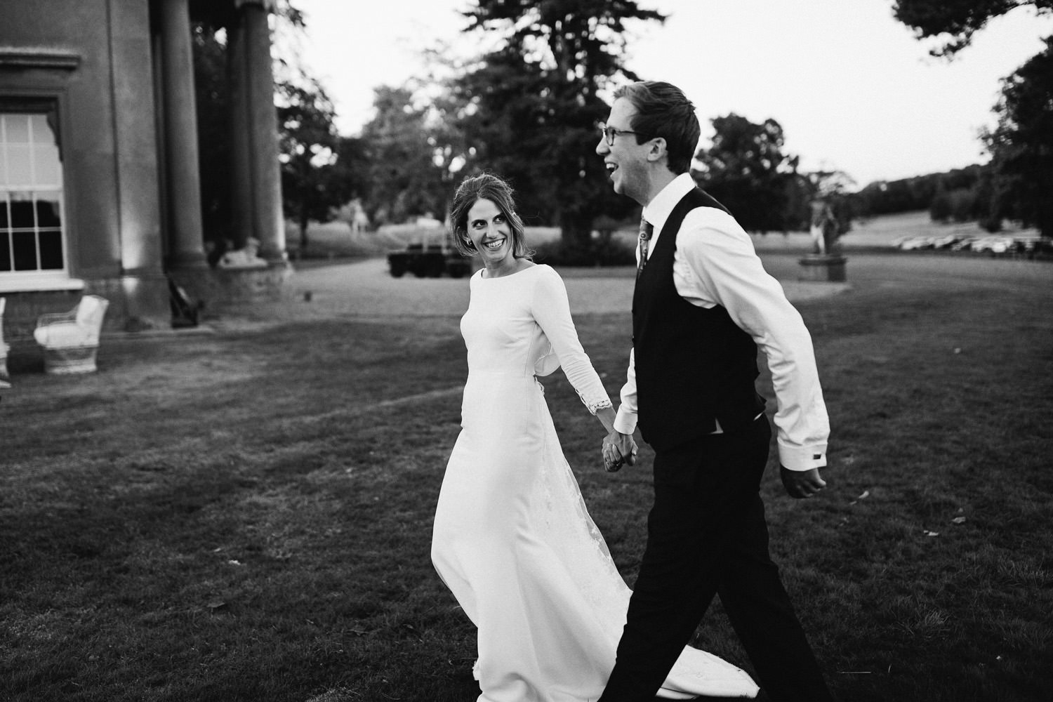 Bride wearing Rime Arodaky walks with groom in the evening light smiling