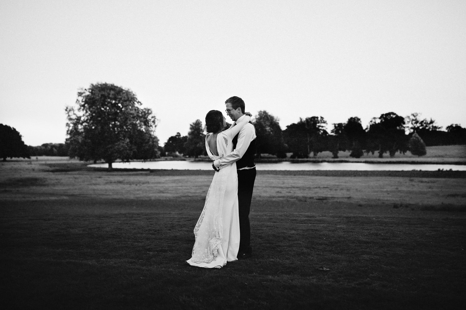 bride and groom hug in evening light at Wilderness reserve in Suffolk