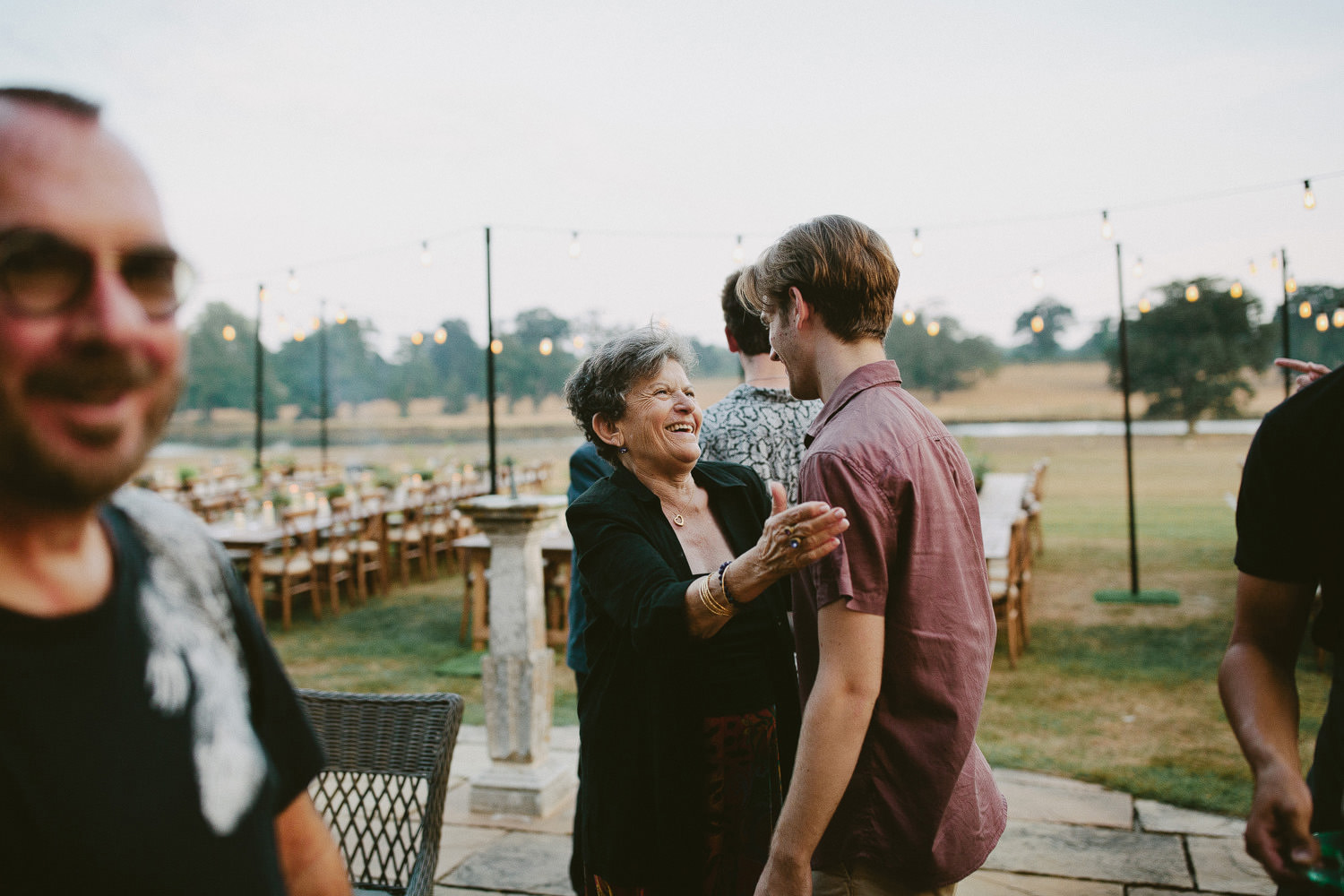 Grandmother smiles at young man on a garden terrace