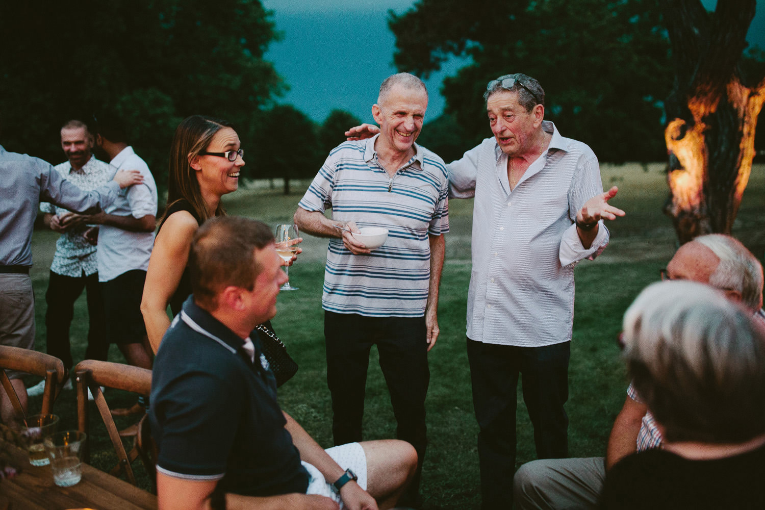 Old men laugh during outdoor party in the evening