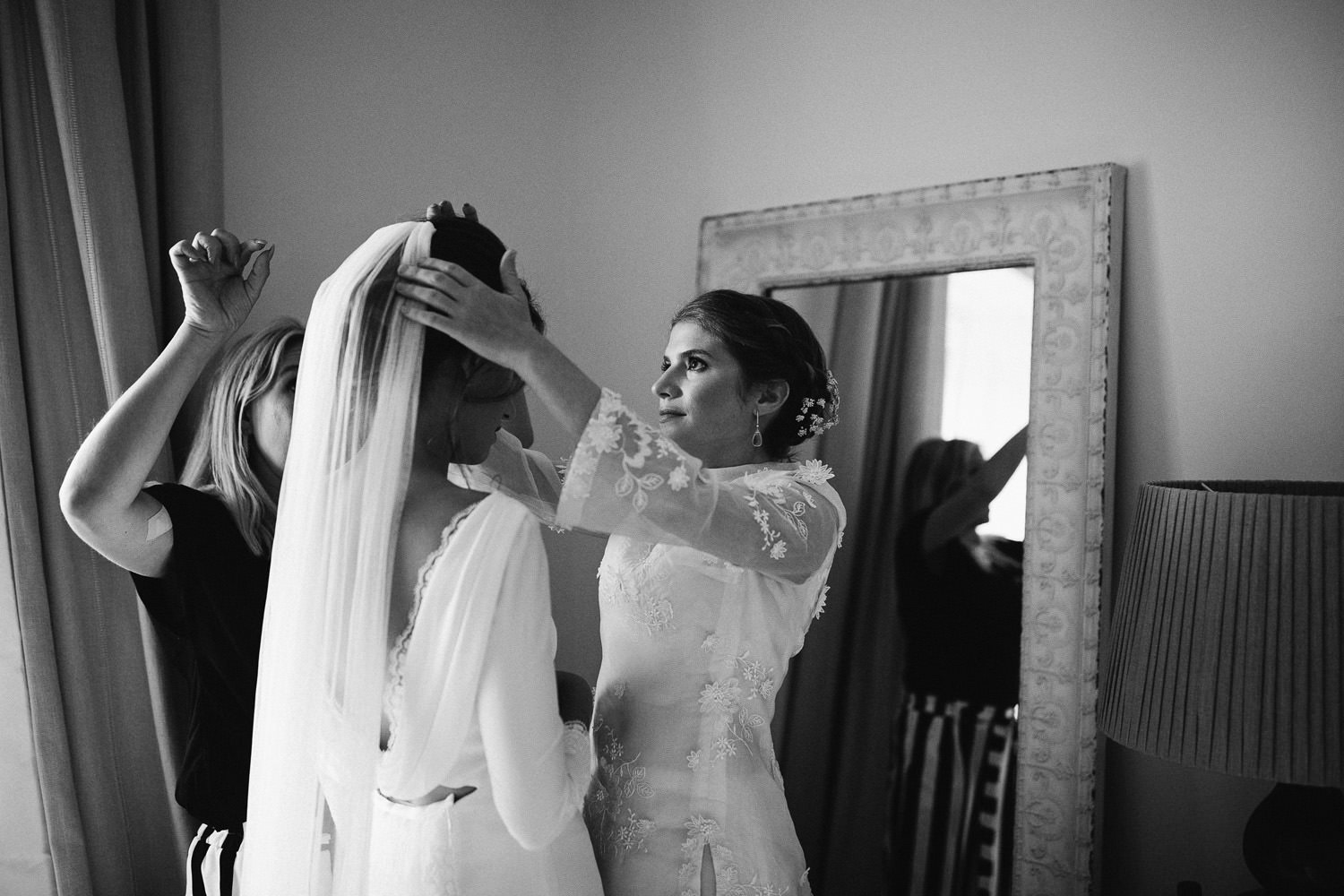 Bridesmaid adjusts the veil of the bride