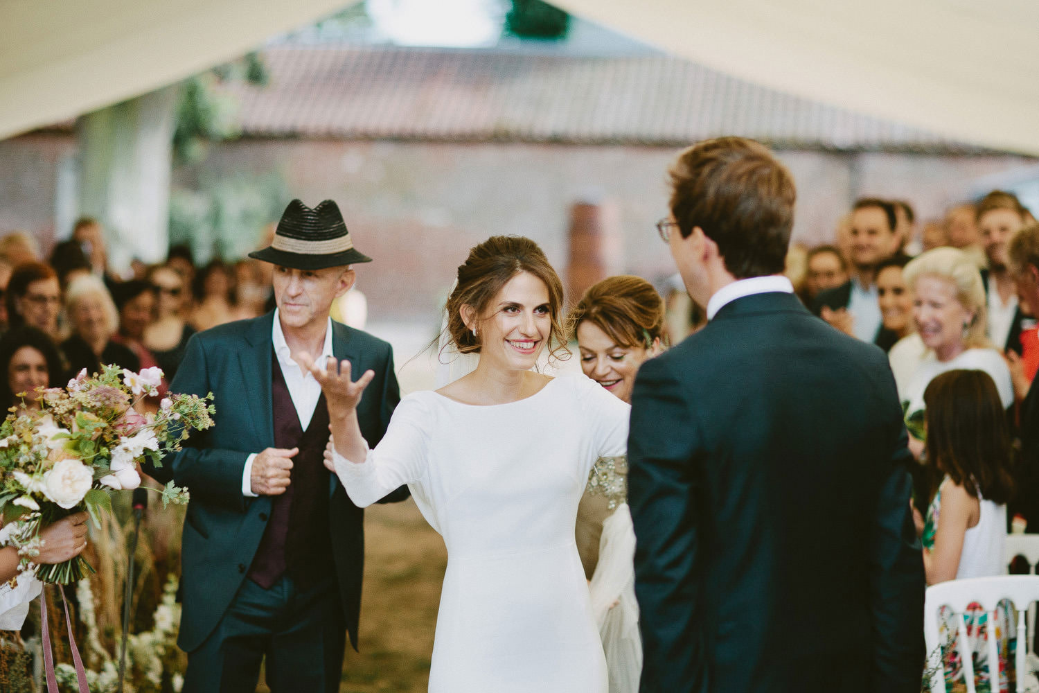 Bride greets groom at the front of a wedding ceremony