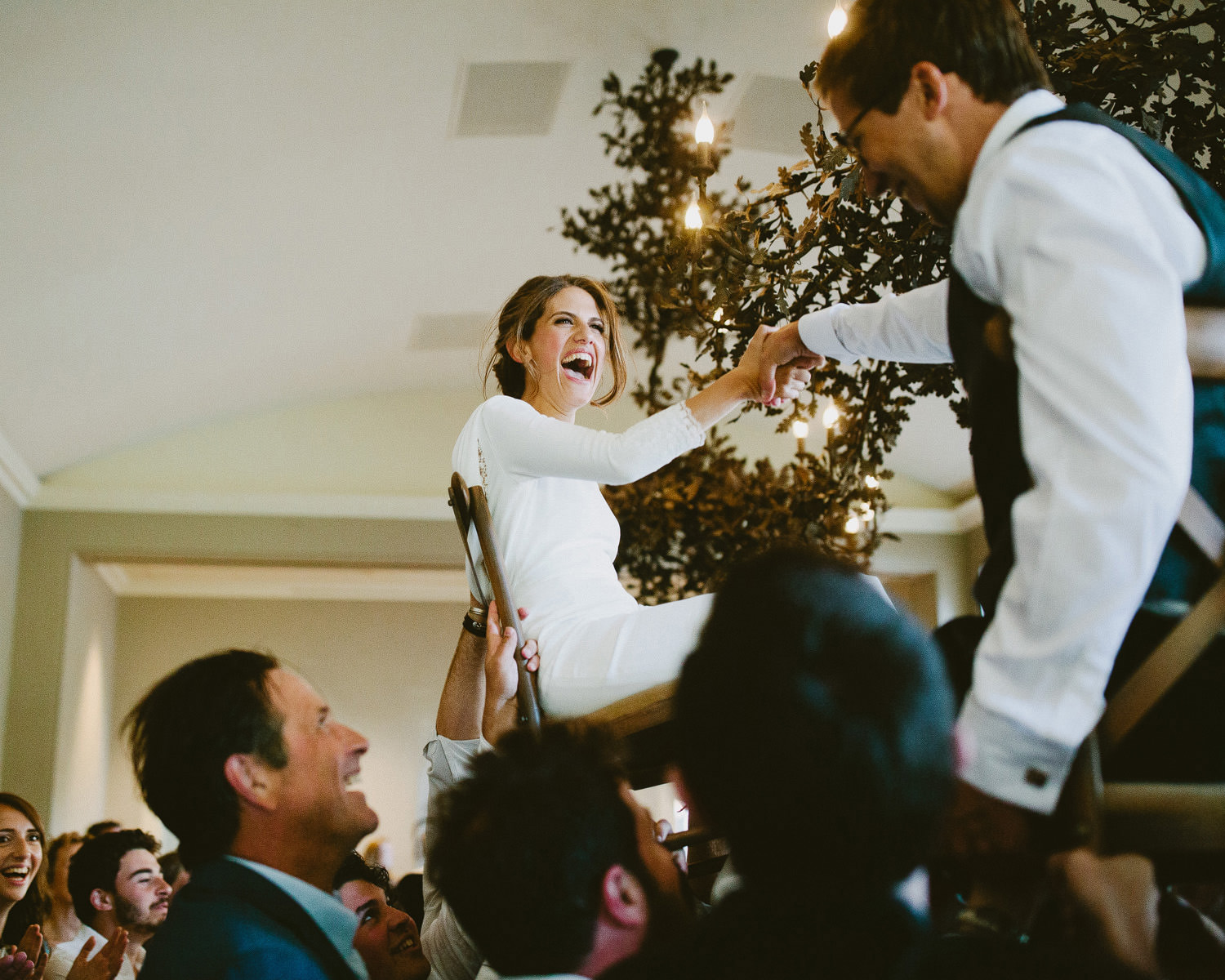 Bride is high in the air on a chair as part of Jewish dancing at Sibton Park