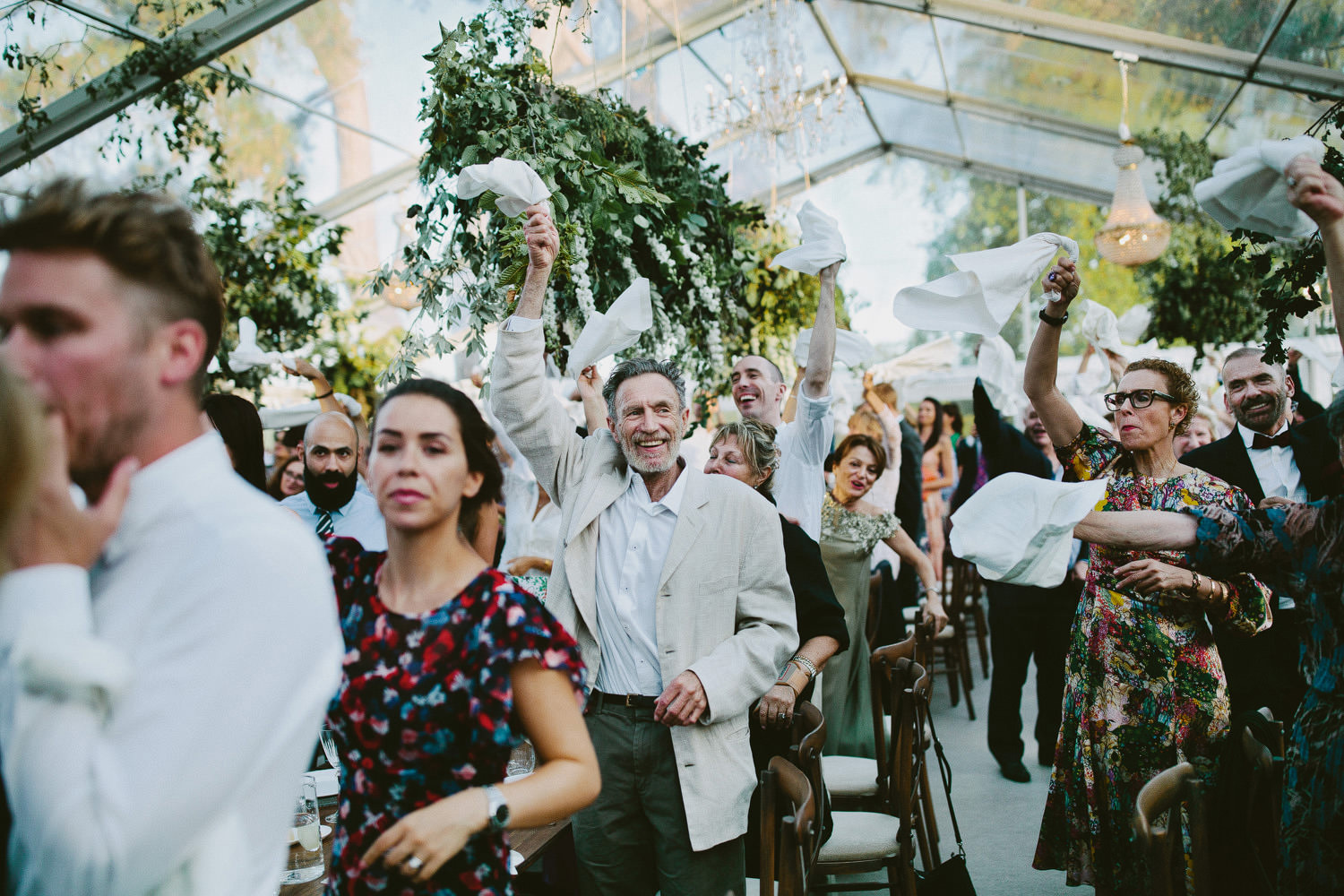 guests wave napkins as bride and groom enter marquee