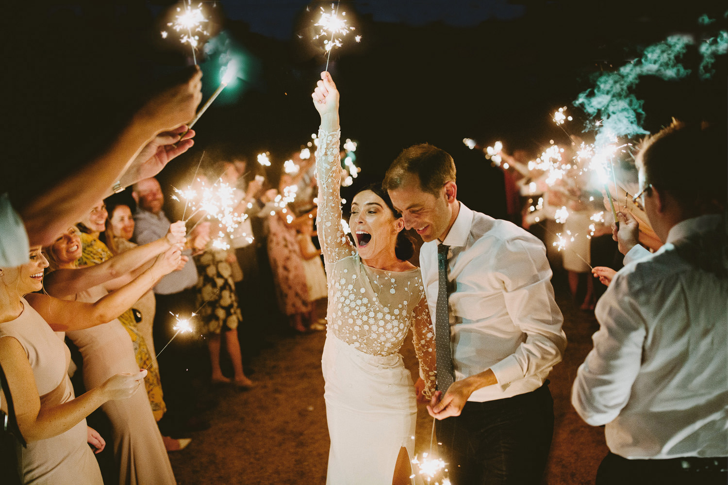 Bride celebrates with a sparkler above her head at night surrounded by friends