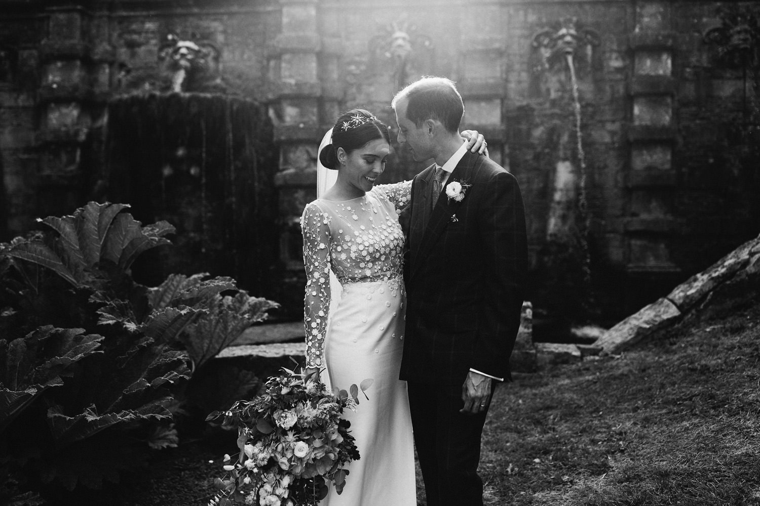 bride and groom kiss in the sunlight during a Cowley Manor wedding