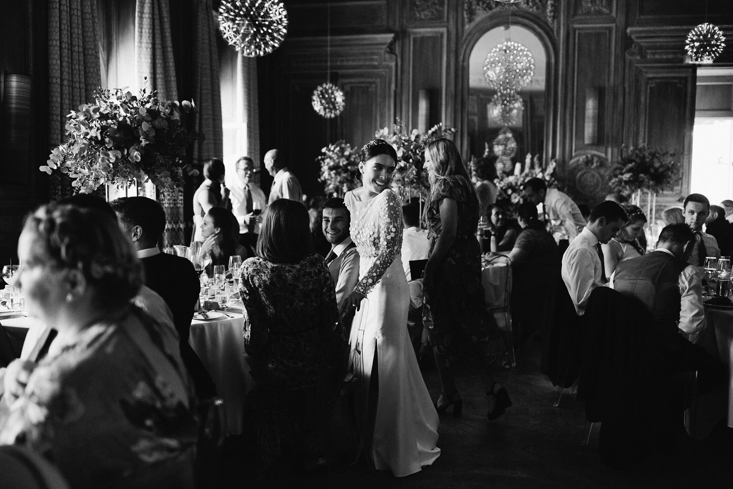 Bride wearing a Rime Arodaky dress smiles during dinner at Cowley Manor