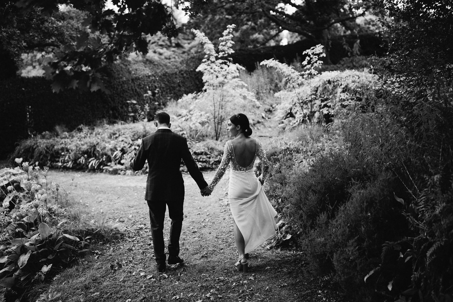 Bride and groom hold hands in the gardens at Cowley Manor