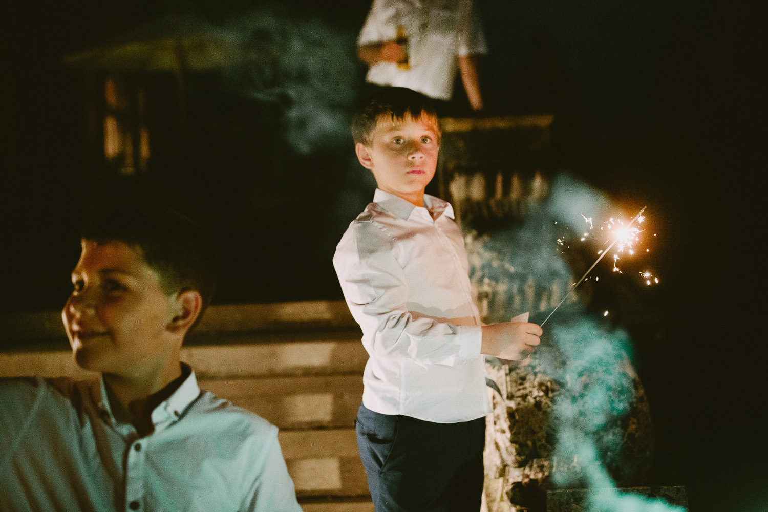 Boy in white shirt holds a sparkler at a wedding in the night