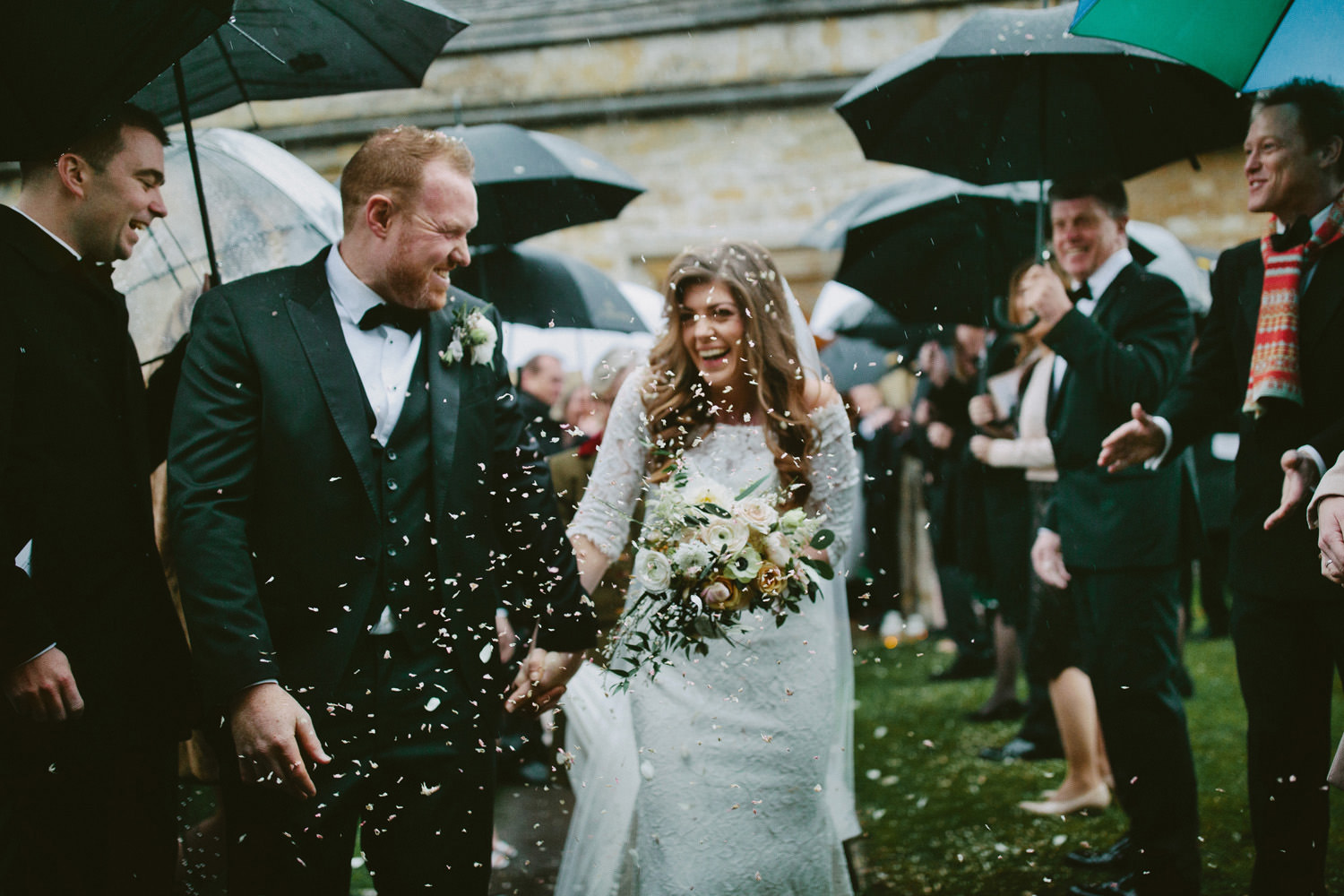 bride and groom smiling with confetti at church near Barnsley House