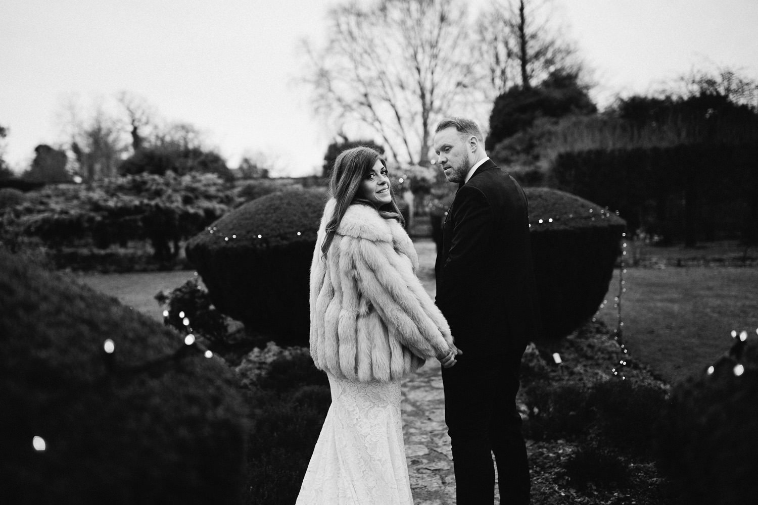 bride and groom walk in gardens at Barnsley House