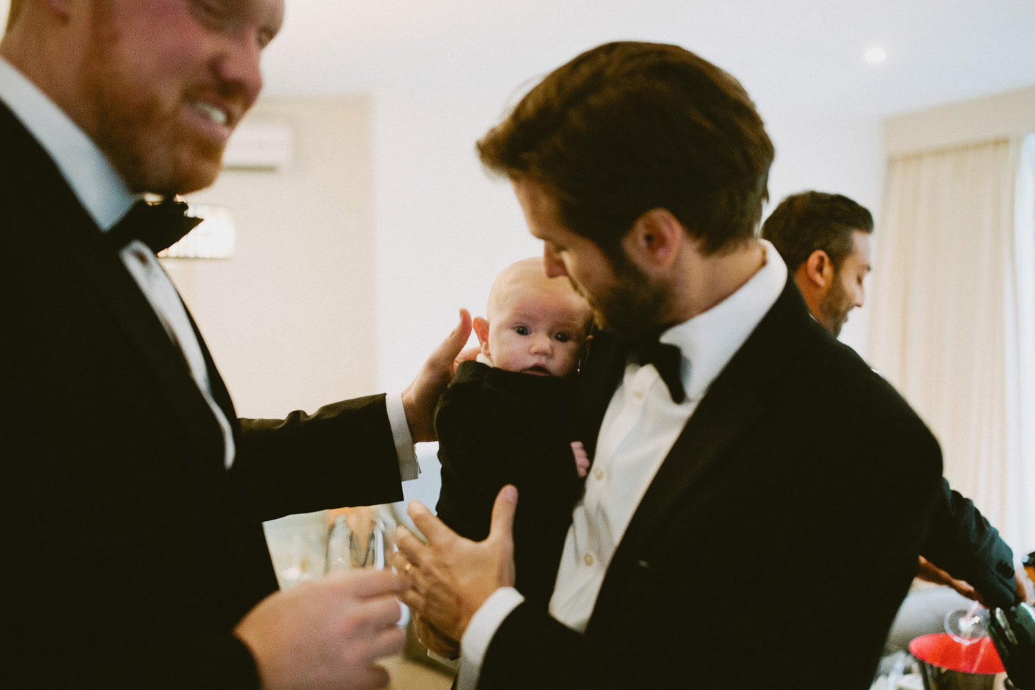 man in black tie holding baby