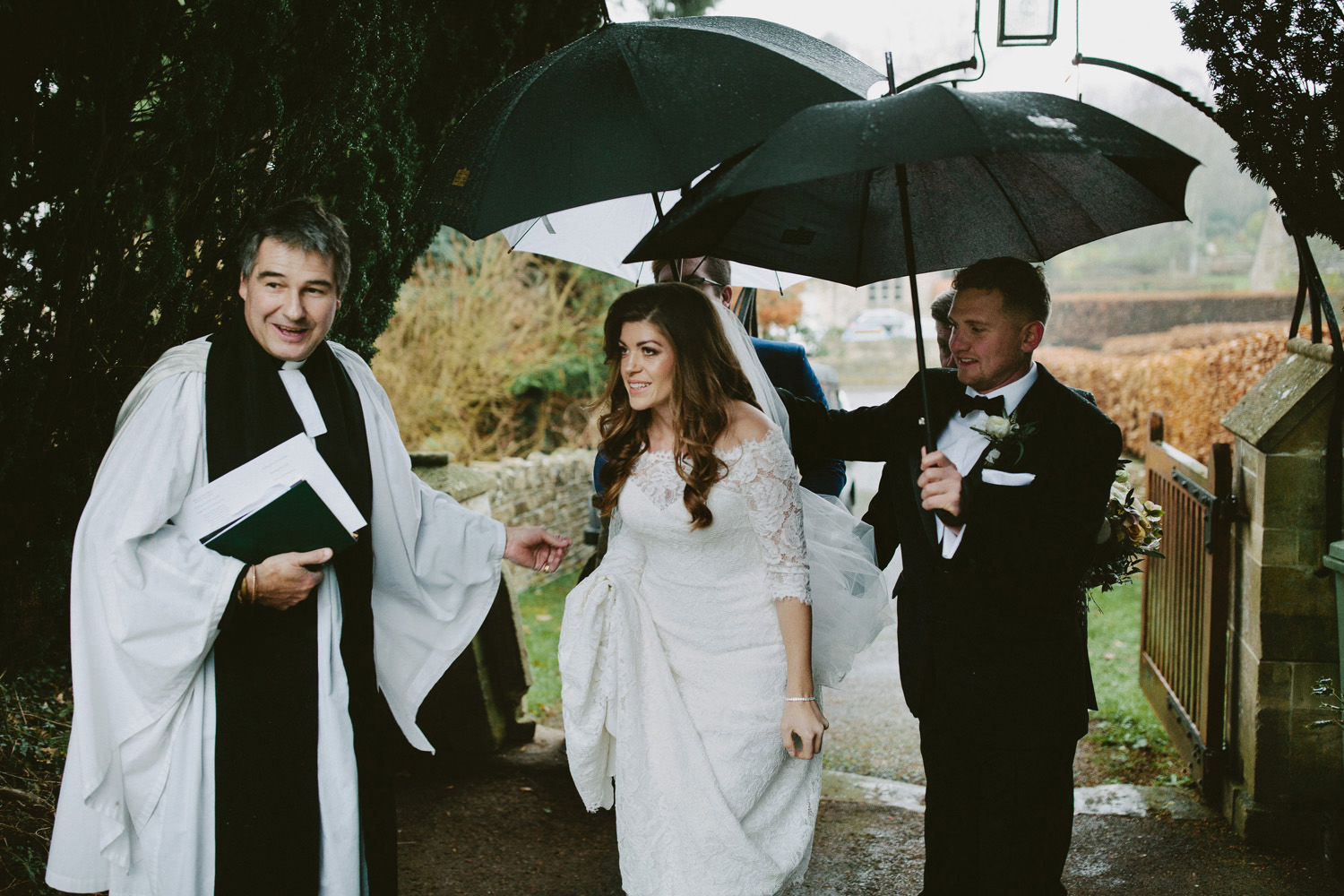 bride arriving at church with umbrellas