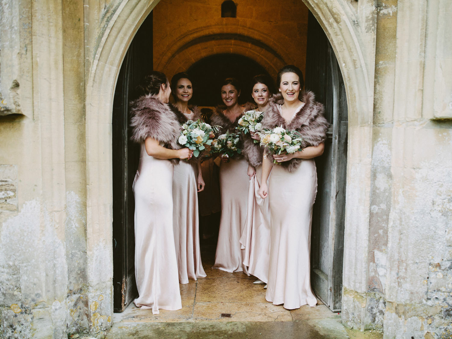 bridesmaids in blush dresses look out from church door