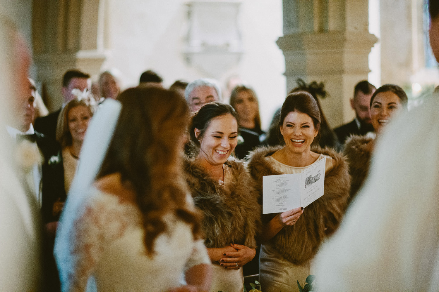 bride turning to seeing smiling bridesmaid at front of church