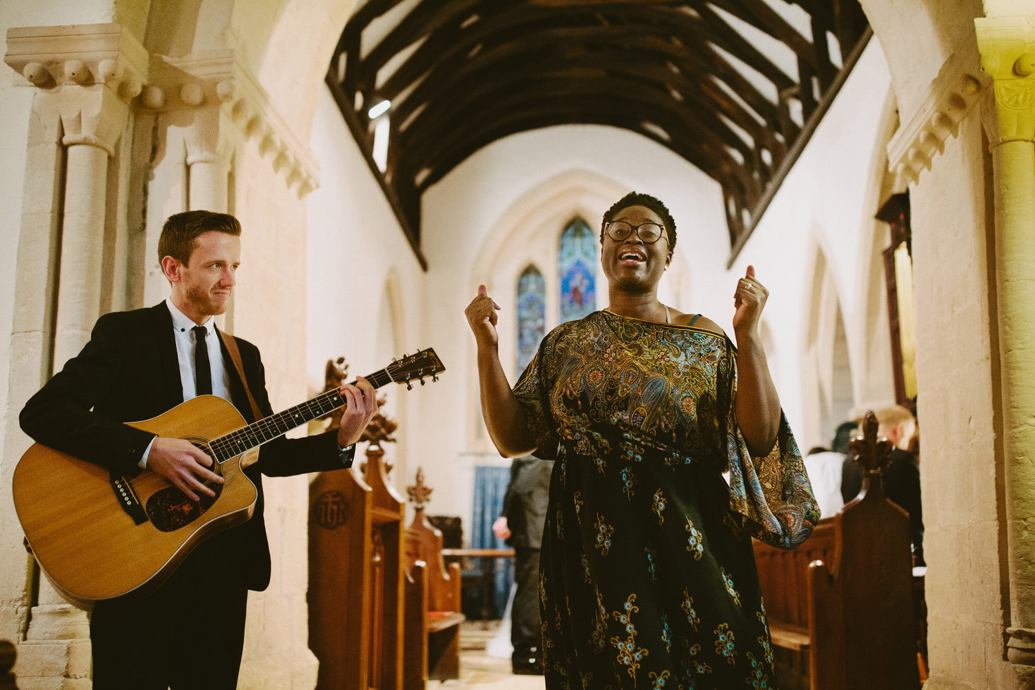soul singer singing in church with guitarist beside her