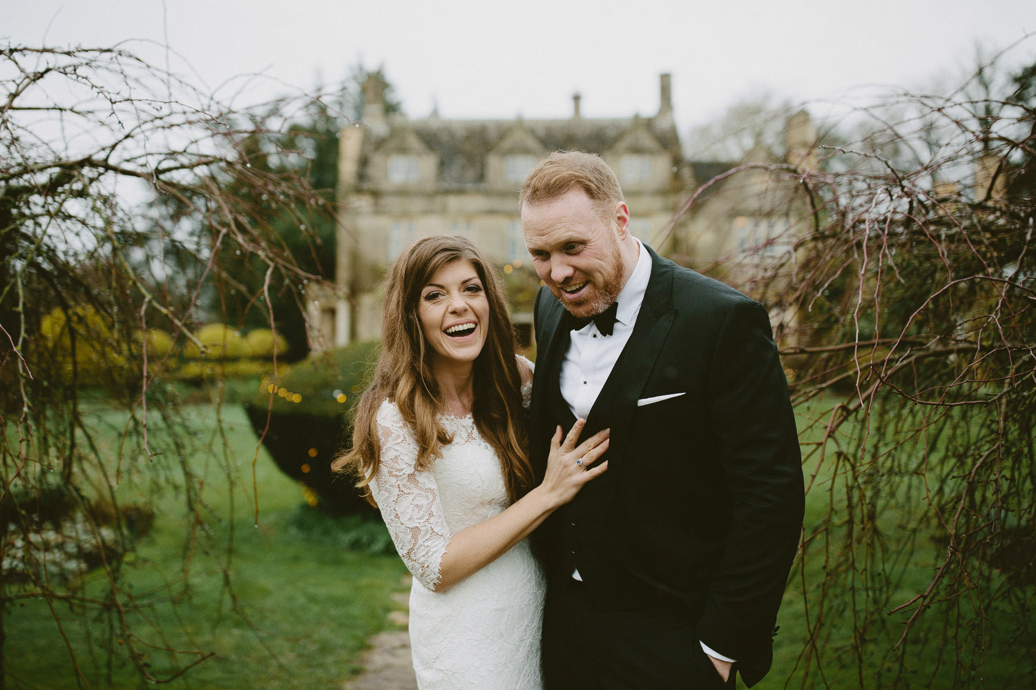 bride and groom smiling in front of Barnsley house