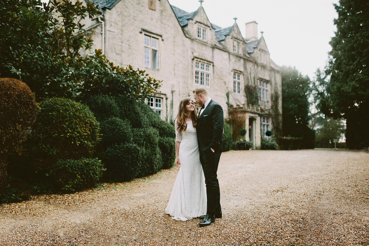bride and groom standing on gravel driveway at Barnsley house