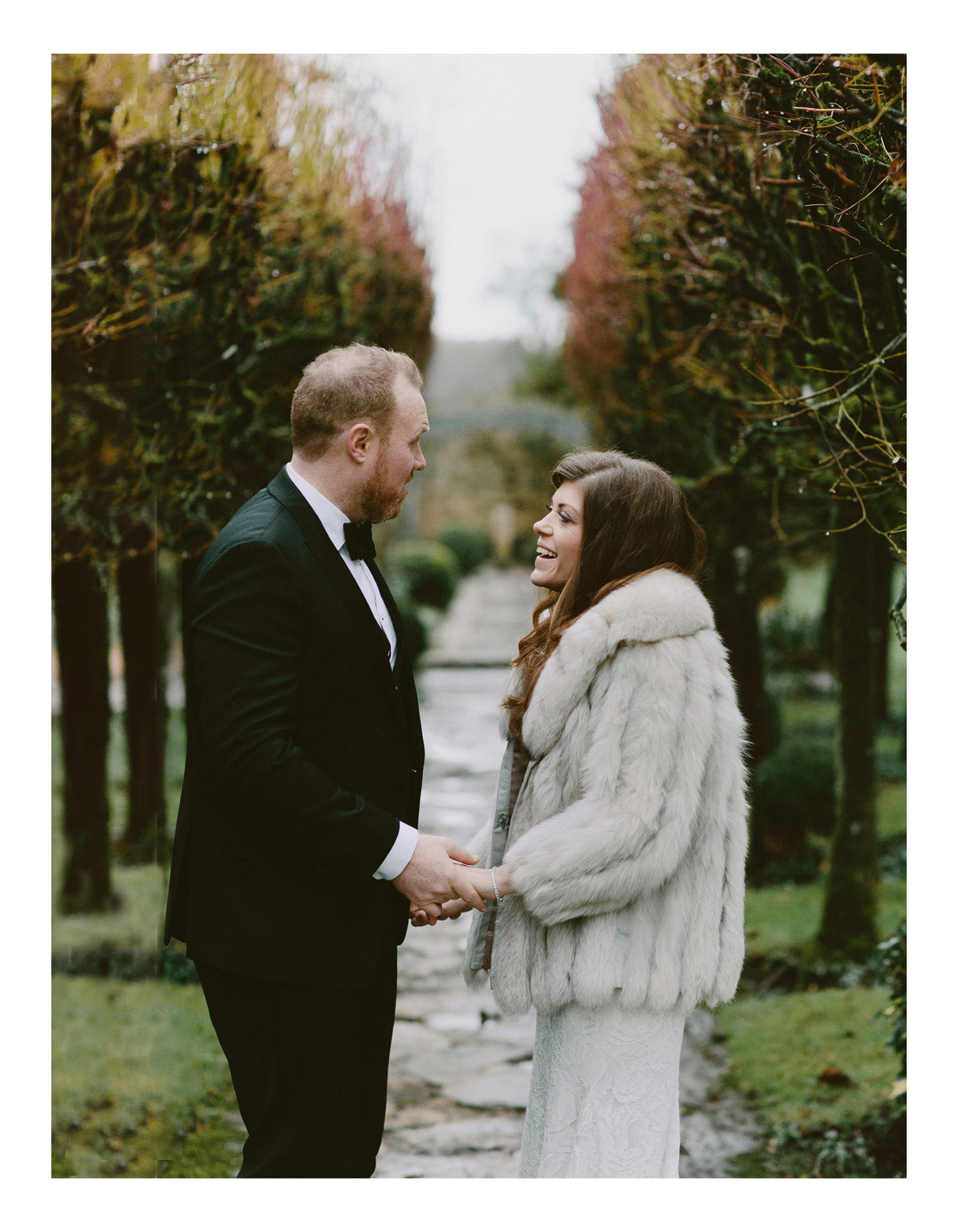 bride in fur coat holding hands with groom in dinner jacket in gardens at Barnsley house