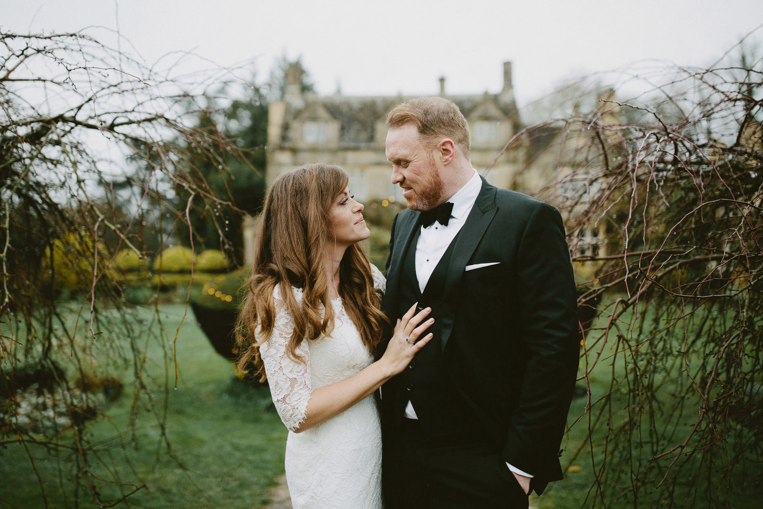 bride and groom smile at each other at Barnsley house