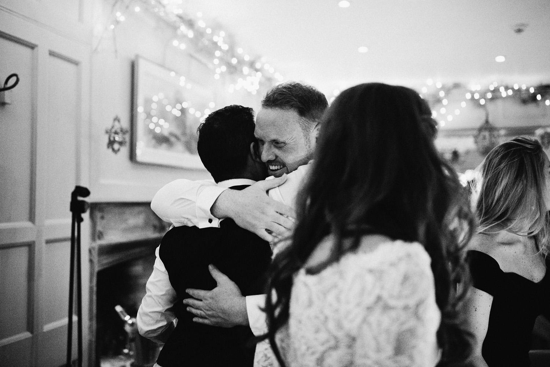 groom huggin best man at Barnsley house