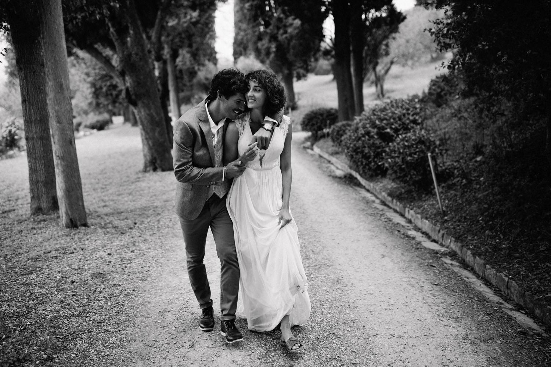 groom hugging bride in avenue of trees in Florence