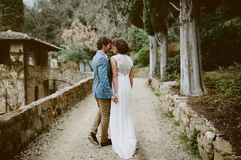bride and groom walking away through gardens of Villa Le Fontanelle