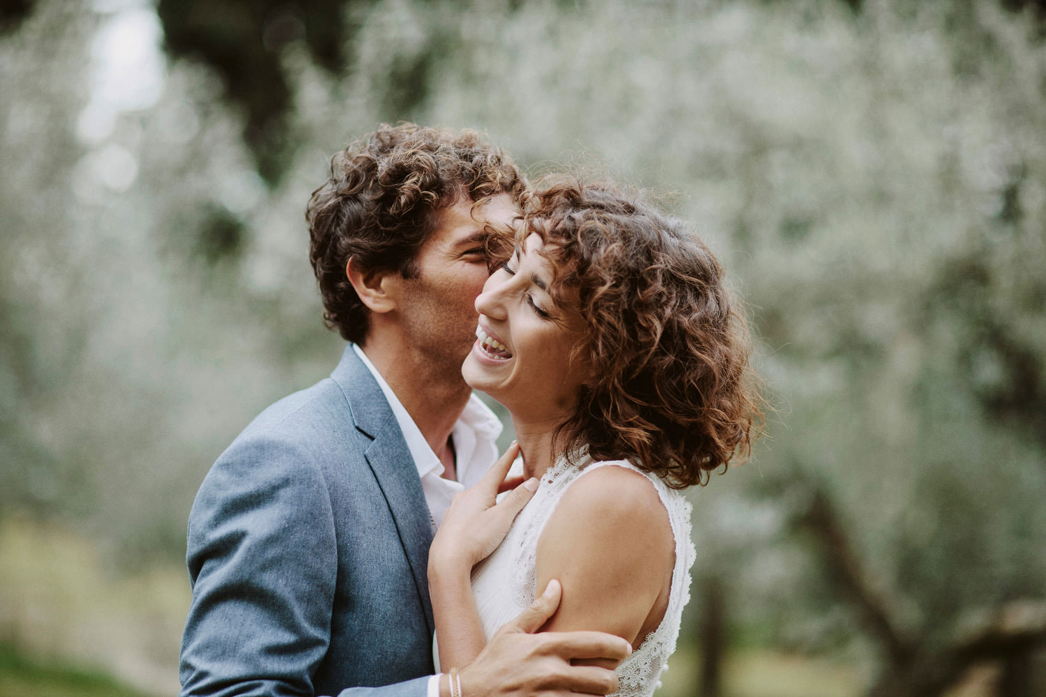 bride and groom laughing surrounded by olive trees