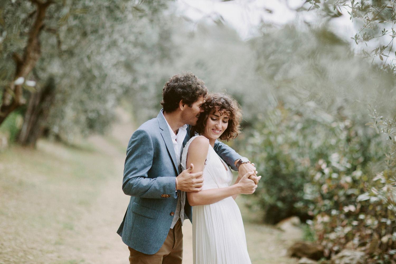 groom in blue jacket hugging bride in olive trees