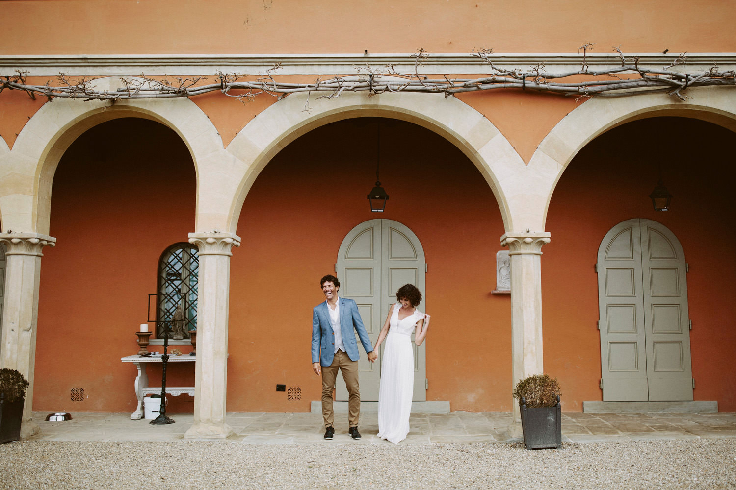 bride and groom laughing in front of wedding venue in Italy