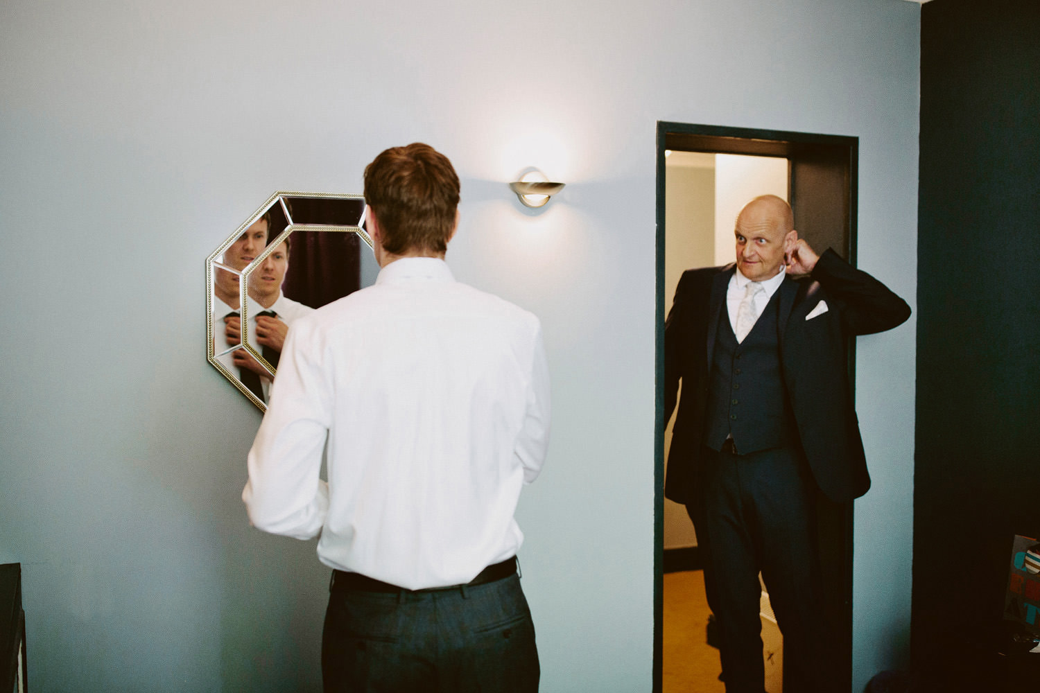 Groom checking himself in mirror at Haweswater hotel