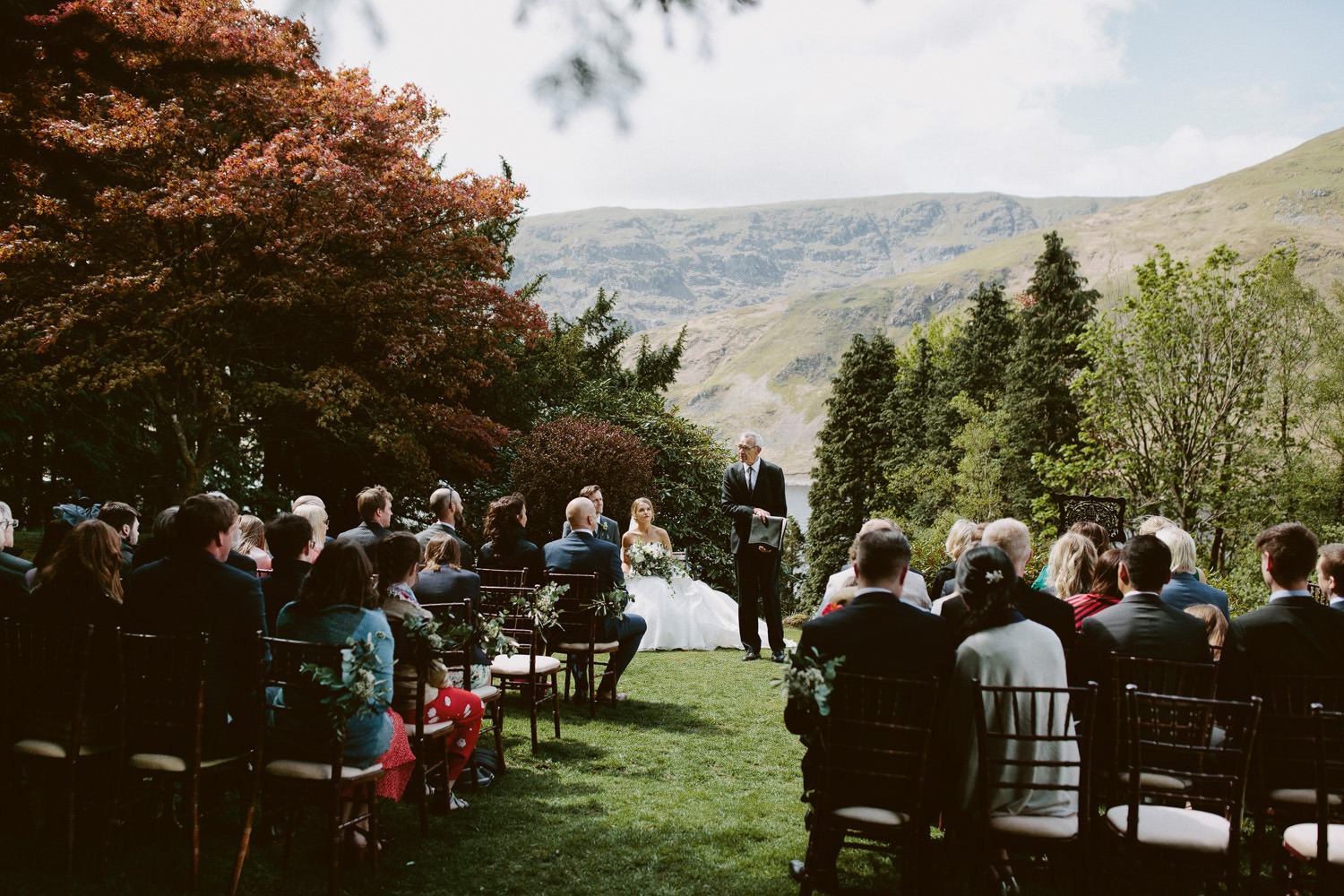 bride and groom sitting during wedding ceremony next to Haweswater reservoir