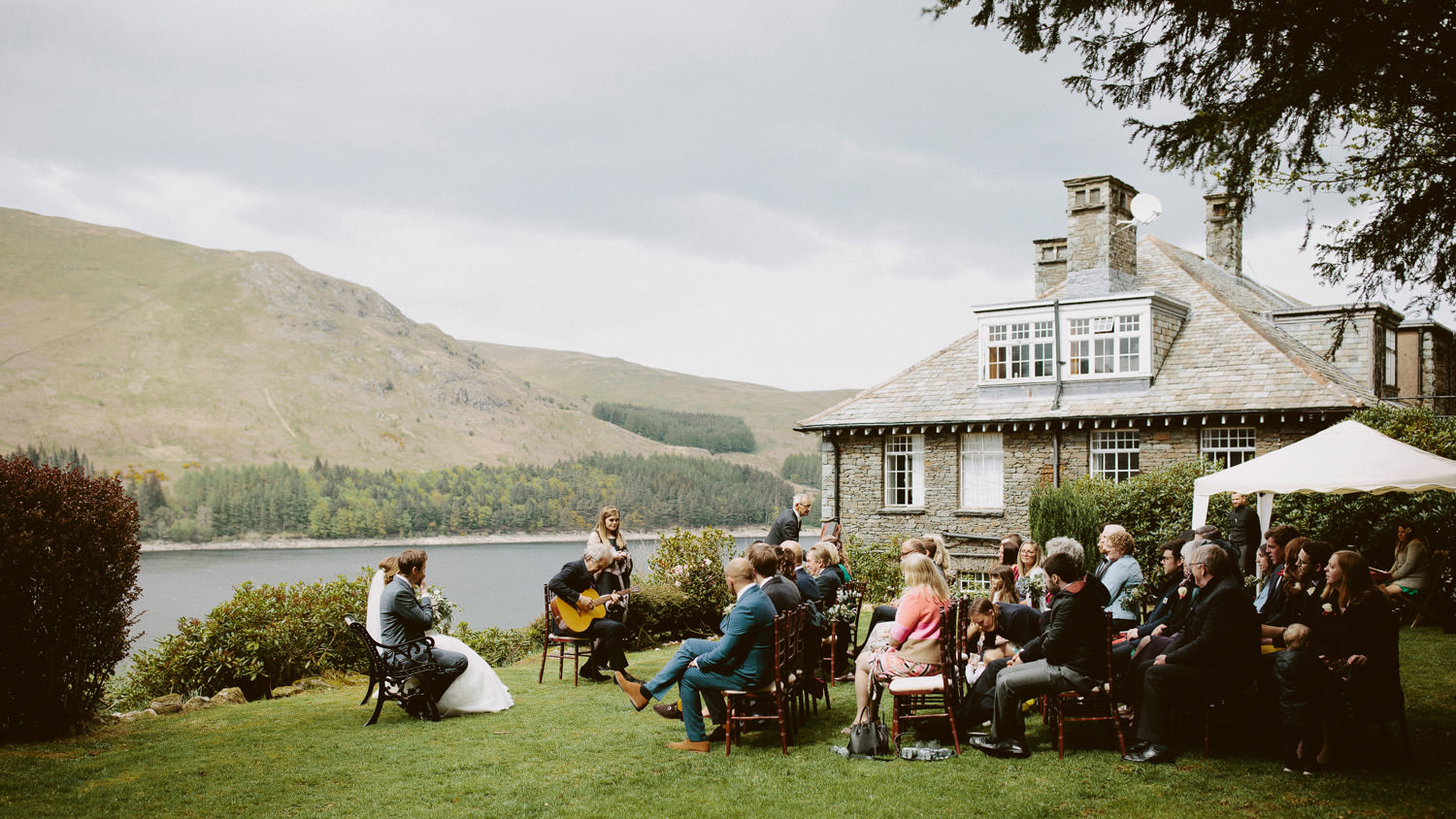 outside wedding ceremony at Haweswater Hotel next to a lake