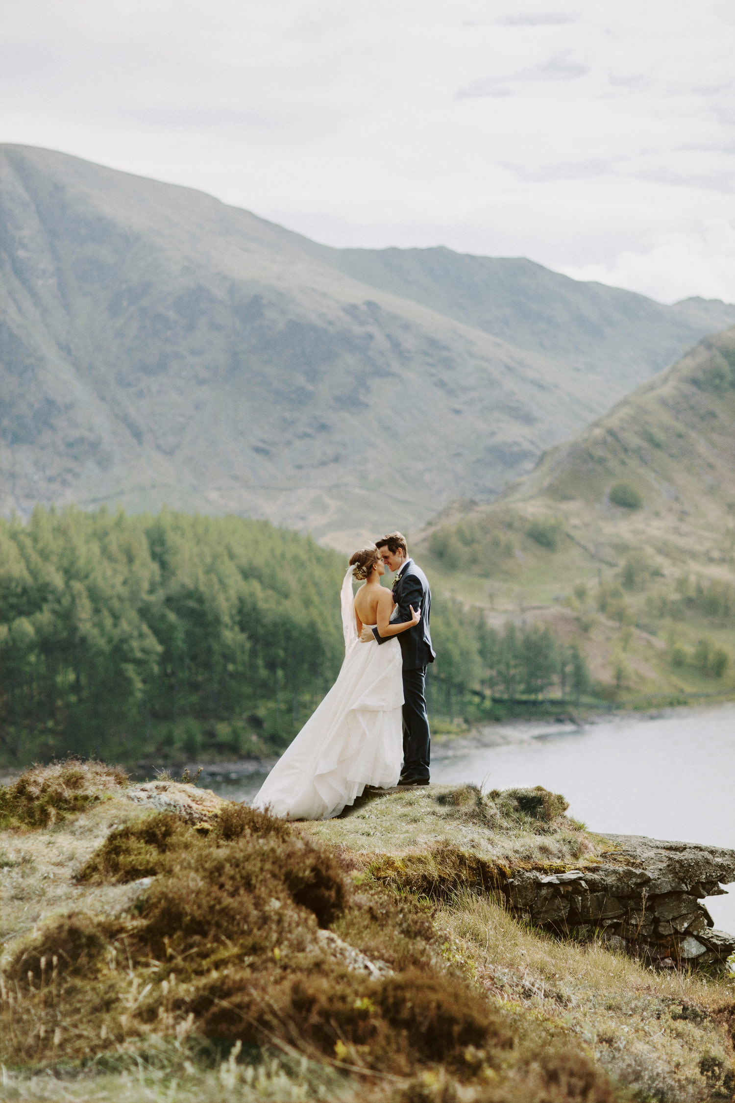 Bride and groom standing in front of valley at Haweswater Reservoir